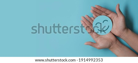 Hand holding paper cut smile face, positive thinking, mental health assessment , world mental health day concept Royalty-Free Stock Photo #1914992353