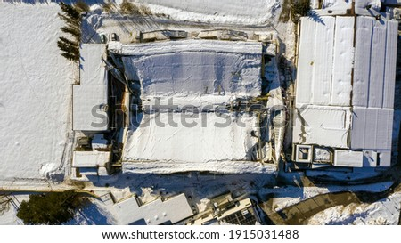 The roof collapsed under the weight of snow. Aerial view of damaged falling roof inside a publica city area. Large collapsed condominium or industrial company. View from above with a drone Royalty-Free Stock Photo #1915031488