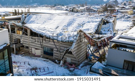 The roof collapsed under the weight of snow. Aerial view of damaged falling roof inside a publica city area. Large collapsed condominium or industrial company. View from above with a drone Royalty-Free Stock Photo #1915031491