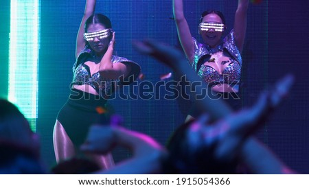 Group of people dance in disco night club to the beat of music from DJ on stage . New year night party and nightlife concept . Royalty-Free Stock Photo #1915054366