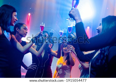 Young people celebrating a party, drink and dance . Group of friend toasting drinks while having fun at the disco club at night . Friendship and nightlife concept . Royalty-Free Stock Photo #1915054477
