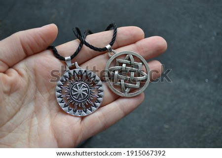Svarga is a symbol and amulet of the Slavs. Warrior symbol. Medallion on black rope. Royalty-Free Stock Photo #1915067392
