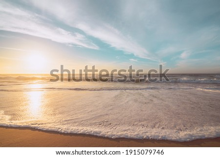 Sunset on the beach. Beautiful tranquil scene of empty sand beach, turquoise colored water, and cloudy sky Royalty-Free Stock Photo #1915079746