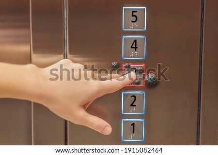 Hand finger press button in elevator with virus. Covid-19 or Coronavirus in the elevator button. Button with virus around the elevator or lift. Infection Control and Social distance concept Royalty-Free Stock Photo #1915082464
