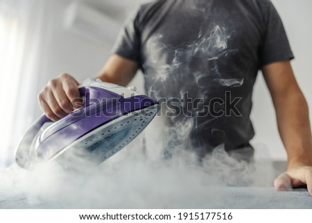 The hot steam from the iron. Powerful film effect of steam on photography. A close-up of a man's body in a grey t-shirt ironing clothes on an ironing board Royalty-Free Stock Photo #1915177516