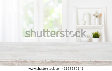 Bleached wooden table top on blurred kitchen summer window background Royalty-Free Stock Photo #1915182949