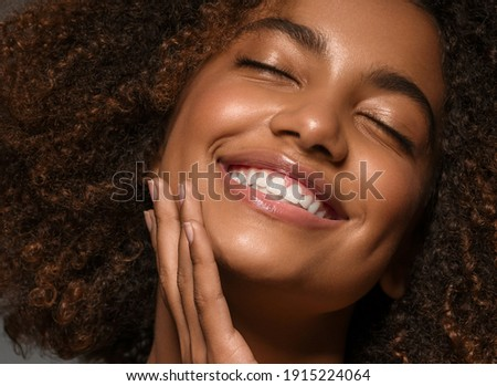 Beautiful african american woman face close up  teeth smile happy positive Royalty-Free Stock Photo #1915224064