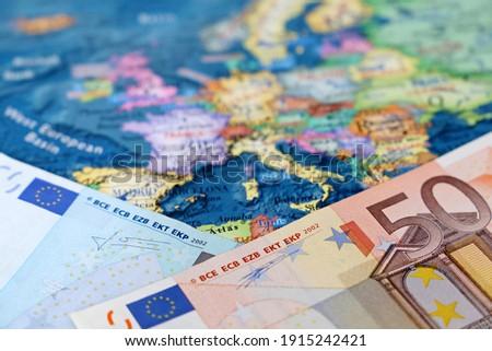 Euro banknotes on the Europe map. Concept of Eurozone, European economy, stock market in EU Royalty-Free Stock Photo #1915242421