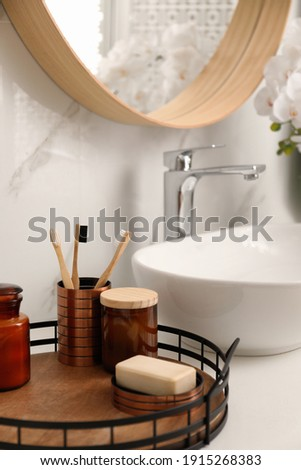 Different toiletries near vessel sink in bathroom Royalty-Free Stock Photo #1915268383