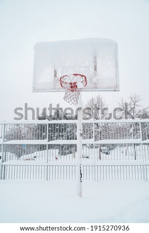 vertical view of frozen basketball outdoors. White conceptual minimalist photo with copyspace. Christmas seasonal cold weather concept.
