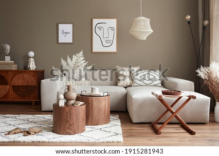Interior design of stylish living room with modern neutral sofa, furniture, mock up poster farmes, dried flowers in vase, coffee tables, decoration and elegant personal accessories in home decor.  Royalty-Free Stock Photo #1915281943