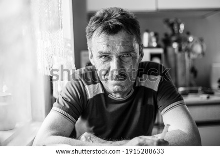 Portrait of a man farmer in his rural home. Black and white photo.