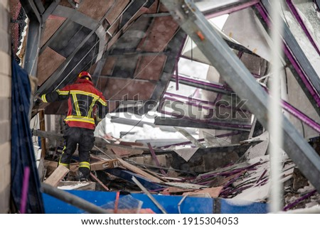 The working moments of the search and rescue teams who were under the rubble in the roof collapse under the weight of snow. Firefighters inside a collapsed house are looking for survivors. Royalty-Free Stock Photo #1915304053