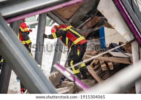 The working moments of the search and rescue teams who were under the rubble in the roof collapse under the weight of snow. Firefighters inside a collapsed house are looking for survivors. Royalty-Free Stock Photo #1915304065