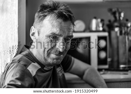A man farmer in his rural home. Black and white photo.