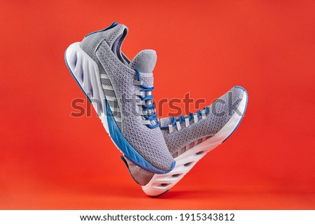 Stability and cushion running shoes. New unbranded running sneaker or trainer on orange background. Men's sport footwear. Pair of sport shoes. Royalty-Free Stock Photo #1915343812