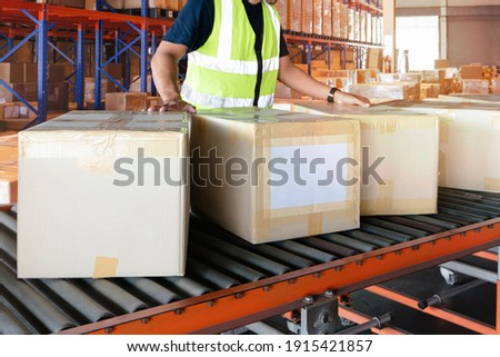 Cardboard boxes sorting on rollers conveyor belt. Worker moving boxes into storage warehouse.  Royalty-Free Stock Photo #1915421857