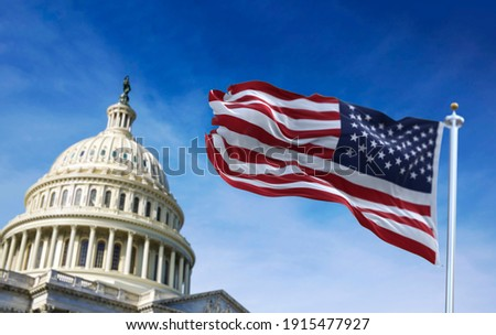 American flag waving with the US Capitol Hill in the background Royalty-Free Stock Photo #1915477927