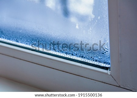 A fragment of a plastic window with condensation of water on the glass. Concept: defective plastic window with condensation, temperature difference, cooling, humidity in the room. Royalty-Free Stock Photo #1915500136