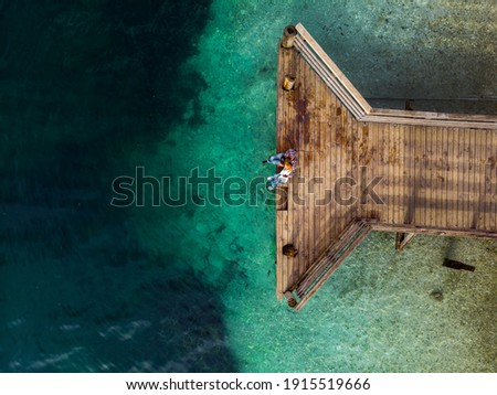 Top down aerial view. A loving couple are sitting on a wooden bridge, a pier. Sunny day, clear water, mountain lake. The concept of romance, outdoor recreation. Relationships and travel. Copy space Royalty-Free Stock Photo #1915519666