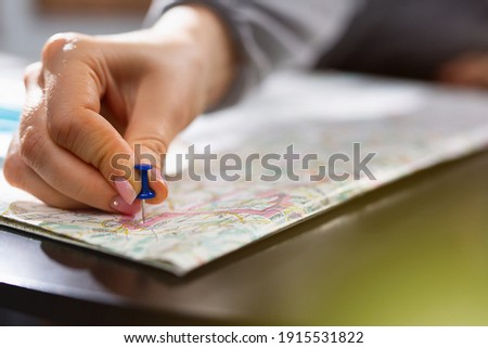 Female hand holding pushpin showing the location of a destination point on a map. Travel destination, pin on the map. Selective focus. Blue pushpin, map on table. High quality photo Royalty-Free Stock Photo #1915531822