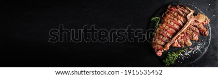 American cuisine. Sliced and roast T-bone or porterhouse beef meat Steak for steakhouse menu. Long banner format, top view. Royalty-Free Stock Photo #1915535452