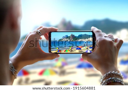 Woman in Ipanema Beach taking a photo with her mobile phone. Photographing with a camera of a smartphone in Rio de Janeiro, Brazil. Royalty-Free Stock Photo #1915604881