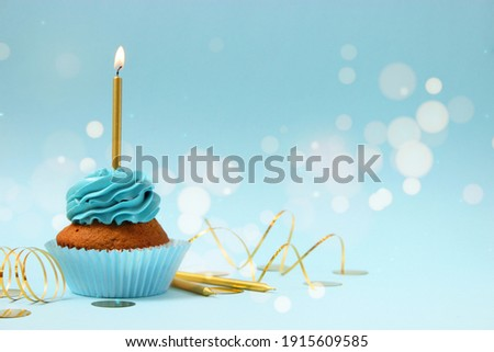 Cupcake with cream and a burning candle for a birthday or other holiday with a shopping plan on a colored background with bokeh lights
