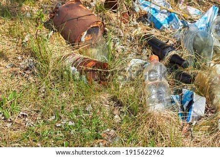 Garbage in forest. People illegally throw garbage into forest. Illegal garbage dump in nature. Dirty environment garbage polluting near footpath in forest. Rubbish, trash Royalty-Free Stock Photo #1915622962