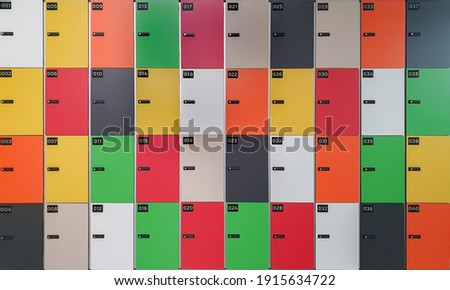 Locker cabinet with locks and numbered lockers in various colors, perpendicular lines Royalty-Free Stock Photo #1915634722