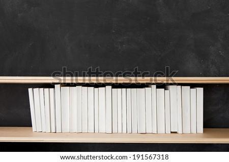 White Books Shelf on Blackboard. A row of all white books sit on a shelf in front of a chalkboard. #191567318
