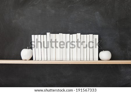 White Books Shelf on Blackboard. A row of all white books sit on a shelf in front of a chalkboard with two white apples. #191567333