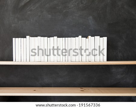 White Books Shelf on Blackboard. A row of all white books sit on a shelf in front of a chalkboard. #191567336