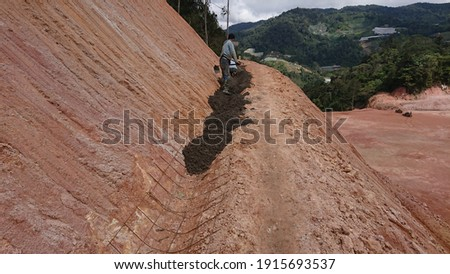 Construction of Berm Drain work at the cutted slope area flr collect all the surface run off and channel to nearest cascading drain as preventative on land slide, slope maintenance and run off.  Royalty-Free Stock Photo #1915693537
