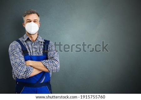 Electrician Workman Or Plumbing Repairman In Face Mask Royalty-Free Stock Photo #1915755760