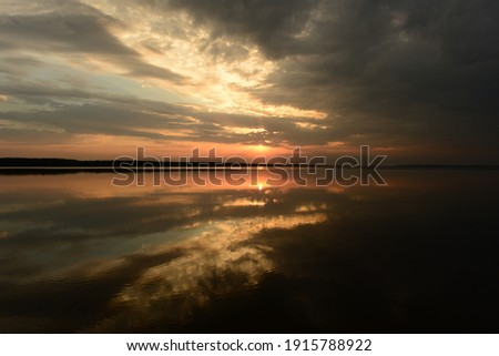 majestic and beautiful sunset in the dark clouds of the sky above the calm water of the lake Royalty-Free Stock Photo #1915788922