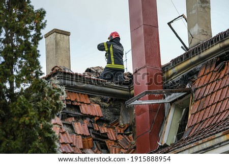 Firefighter inside a collapsed roof of a house is looking for survivors. House rooftop damage. Charred roof trusses and burnt furniture. A blazing fire burns roof rafters. Translation:''Firefighters'' Royalty-Free Stock Photo #1915888954