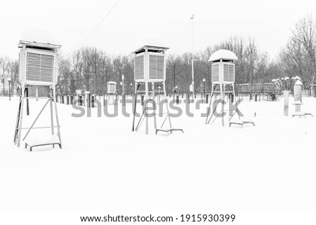 Meteorological booths for student training. High snow cover. Frosty weather with stratus clouds. Louver booth for meteorological instruments. Rain gauge and pluviograph. Royalty-Free Stock Photo #1915930399