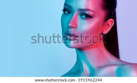 High fashion model metal silver lips and face woman in colorful bright neon UV blue and purple lights, posing in studio, beautiful girl, glowing makeup, colorful makeup. Glitter Bright Neon Makeup Royalty-Free Stock Photo #1915962244