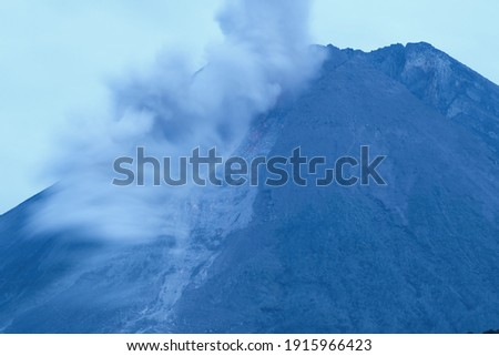 Blurry and close-up picture of Merapi volcano eruption under the blue hour time, captured in long exposure.