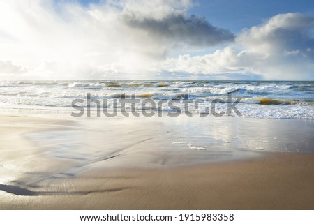 Panoramic view of Baltic sea from sandy shore (sand dunes). Dramatic sky with glowing clouds, sunbeams. Waves, water splashes. Idyllic seascape. Warm winter weather, climate change, nature. Denmark Royalty-Free Stock Photo #1915983358