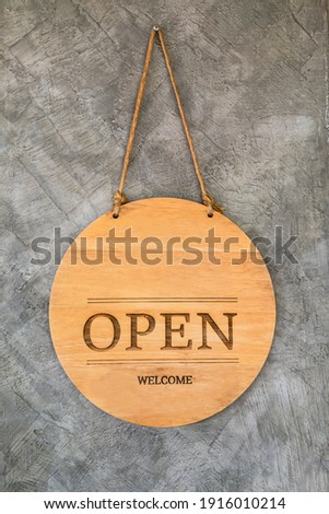 Round wooden open sign on cement background