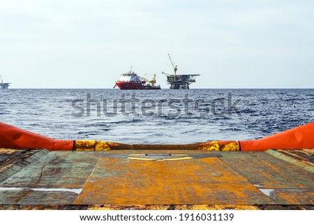 An anchor handling tug boat leaving an offshore oil production platform with a construction vessel moored next to it Royalty-Free Stock Photo #1916031139