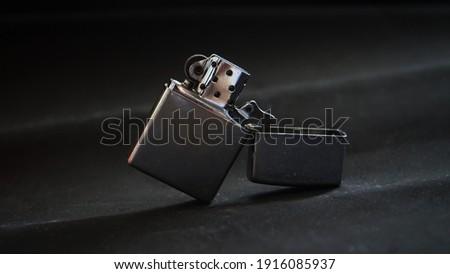 metal gasoline lighter on black background                              Royalty-Free Stock Photo #1916085937