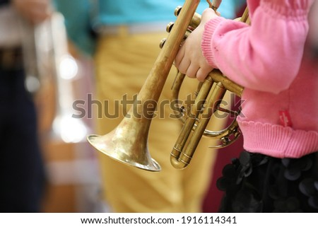 A girl child musician in a pink sweater holds a musical wind instrument trumpet in her hands on a blurred background of an adult teacher.The concept of school music education Royalty-Free Stock Photo #1916114341