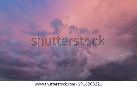 Dramatic sky and a view of infinity. Clouds in sunset, place for copy space. Look up to the sky, amazing desktop wallpaper. Purple pink illuminated clouds in the evening heaven. After the storm