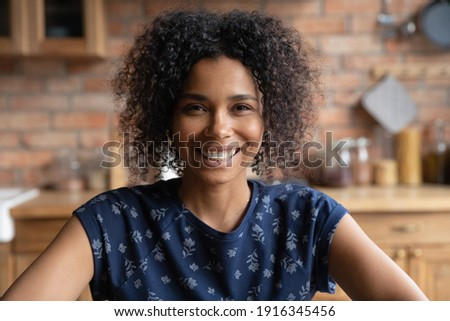 Head shot portrait smiling curly African American young woman looking at camera, involved in online conference, video call, influencer blogger recording vlog, tutorial, mentor coach shooting webinar