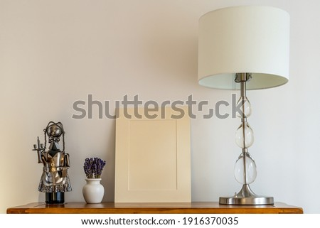 close up of still life  mock up beige picture mount, lamp with shade and china pot  and lavender floral arrangement and wine holder