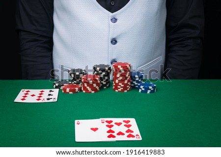 a set of poker chips and cards on the background of the croupier's body in a black shirt and a light vest