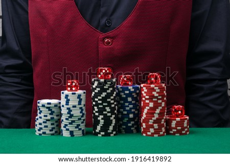 a set of poker chips on the background of the croupier's body in a black shirt and a red vest